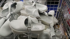 White clogs (oxfords) and panorama on t-shirts in the store Stock Footage