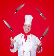 Cheerful cook juggle with knife Stock Photos