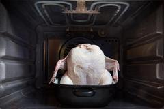Raw chicken in a roasting pan in oven Stock Photos
