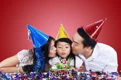 parents kiss their child in birthday party - stock photo