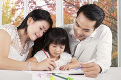 two parents assist their child studying - stock photo