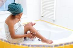 Woman creams her leg in bathroom Stock Photos