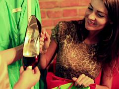 Woman showing new high heels to her friend in the boutique Stock Footage