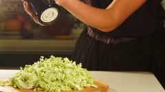 Woman uses pepper mill for cabbage salad. Closeup. Stock Footage