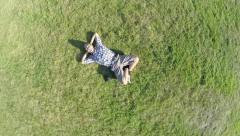 Aerial of man lying on grass, extreme zoom-out, Earth globe, click for HD - stock footage