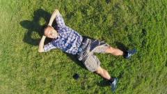 Young smiling male lies on grass, aerial vertical shot, zoom-out, click for HD Stock Footage