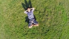 Happy man lying on grass hands behind head, aerial shot, click for HD Stock Footage