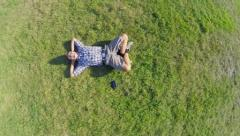 Aerial, young positive man lying on ground hands behind head, click for HD Stock Footage