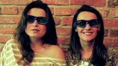 Women watching movie in 3d glasses and sitting on the sofa Stock Footage