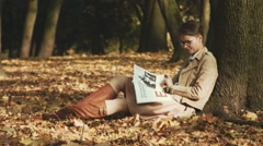 Young woman reads under a tree. Autumn, fall foliage. Stock Footage