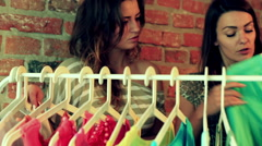 Woman trying shirt and showing price to her friend in the shop Stock Footage