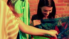 Woman showing new scarf to her friend in the boutique Stock Footage