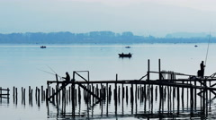4K Blue tranquil scenery with small fishing boats and silhouette of fishermen Stock Footage