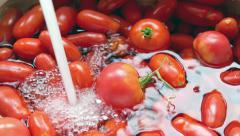 4k Hand washing fresh tomatoes under tap water from kitchen sink Stock Footage