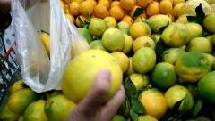 Woman hands choosing and picking orange in a department store Stock Footage