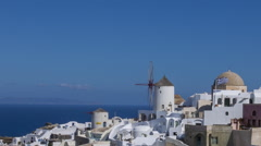 Santorini Oia - Windmill, buildings and Greek flag flying Stock Footage