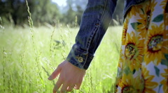 Young Woman Walks Through Tall Grass, Close Up Of Her Hand Feeling Grass Stock Footage