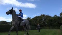 Horse Racers on horses enter the racing course Stock Footage