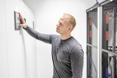 Engineer adjusts air conditioner in datacenter Kuvituskuvat