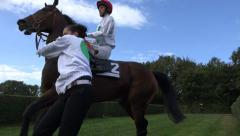 Restive racing horse with jockey leading to the course Stock Footage