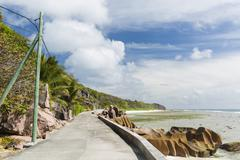 Low tide at the wild east coast of la digue, seychelles with the only road in Stock Photos