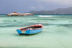 a little blue boat in a lagoon in la digue, seychelles with view to praslin - stock photo