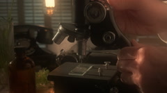 Vintage scientist working with a microscope colorized Stock Footage