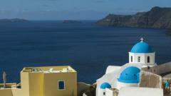 Santorini Oia - Tilt down from blue sky to Blue Domed Buildings with man walk Stock Footage