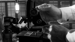 Vintage scientist working with a microscope BW Stock Footage