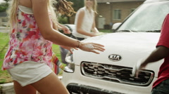 Medium shot of siblings having water fight and washing car / Pleasant Grove, - stock footage