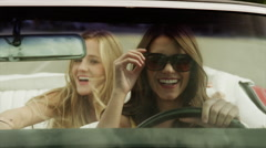 Close up tracking shot of young women driving convertible car / Pleasant Grove, Stock Footage
