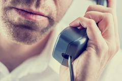 man listening to a telephone conversation - stock photo