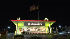 McDonalds Golden arches restaurant, waving usa flag Stock Footage
