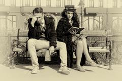 Young couple in quarrel sitting on bench in old town Stock Photos