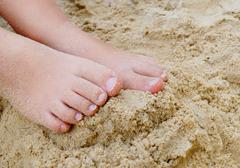 Small Child's Feet in Beach Sand - stock photo