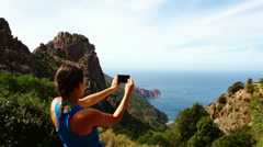 Young woman uses a smartphone to video a beautiful view in the sea HD Stock Footage
