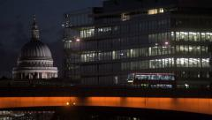 A Double-Decker Bus crosses London Bridge in London at night - stock footage