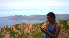 Woman texting a message in the mountains  HD Stock Footage