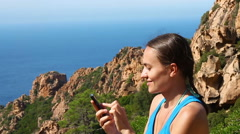 Woman texting a message in the mountains, slow motion  HD Stock Footage