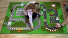 Child fascinated by the automotive game on the floor in the room Stock Footage