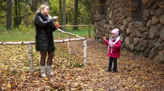 Mom and daughter blow bubbles in the park on a background of yellow foliage Stock Footage