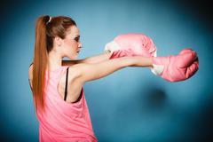 Stock Photo of female boxer wearing big fun pink gloves playing sports