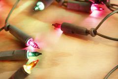 closeup of christmas lights glowing on wood - stock photo
