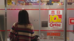 Lady walking into a pachinko store in Kyoto Stock Footage
