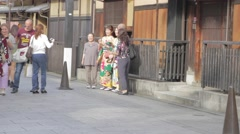 Tourist posting for pictures with Gion women wearing kimono's Stock Footage