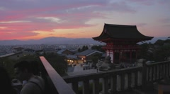 pan golden red sunset of Kyoto from Kiyomizu-dera - tourists take pictures - stock footage