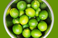 fresh limes in metal bowl top view photo. - stock photo