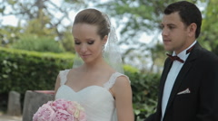 The groom comes to the bride behind,hugs and kisses her Stock Footage