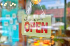 Open sign broad through the glass of window Stock Photos