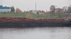 Long barge for wood transportation with timber on open deck moving on river Stock Footage